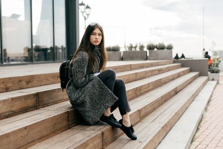 stylish young dark-haired girl in a gray coat sits on the steps in the city streets, posing