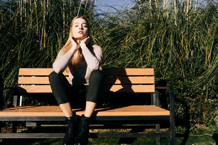 attractive beautiful young blond model girl sitting on a bench outdoors, enjoying the sun and posing