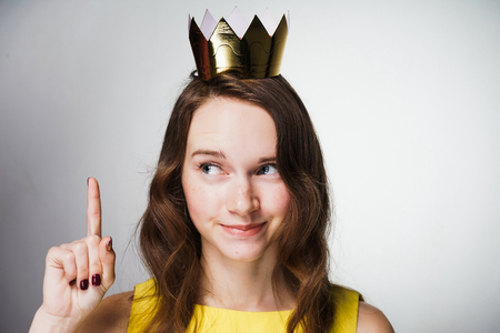 a cute young girl in a yellow dress lifted her index finger up, a golden crown on her head, an idea appeared