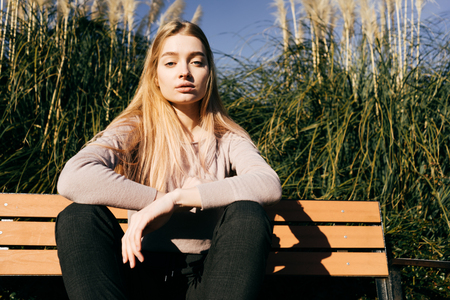 confident attractive blonde girl sitting on a bench outdoors, in a park, enjoying the sun and warmth Stock Photo