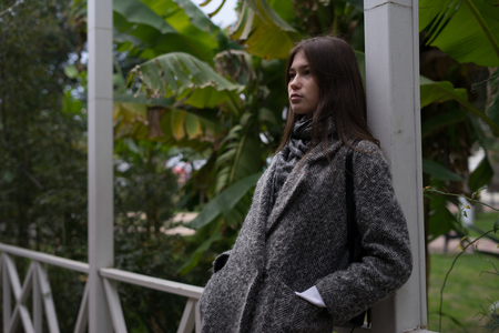 a stylish dark-haired girl in a gray coat stands against the background of green trees, thinks about something
