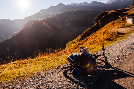 A bicycle with a large backpack stands on the side of the road against the backdrop of the mountains