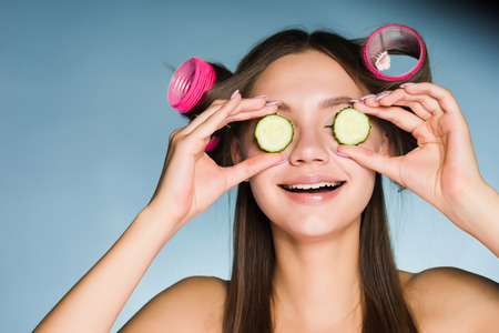 woman on blue background smiling holding cucumber slices