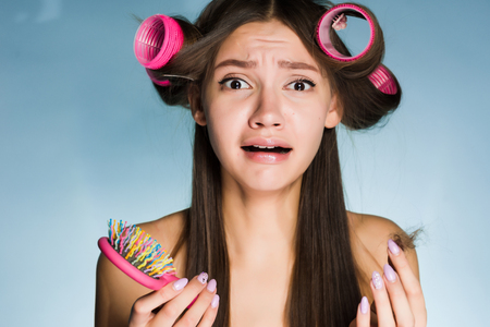 a frustrated woman with curlers on her head on a blue background holds a comb Stock Photo