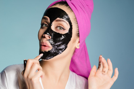 a surprised woman with a towel on her head puts a mask on her face Stock Photo