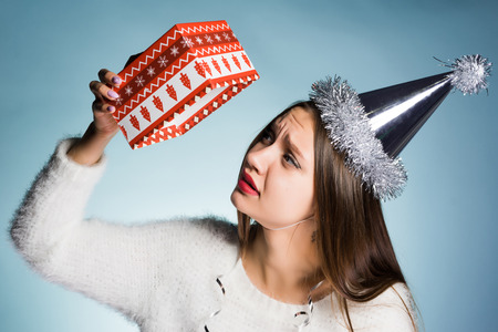sad woman in a festive hat holds an empty box from under the gift Stock Photo