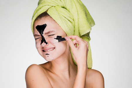 dissatisfied young girl with a green towel on her head removes the black mask from her face, it hurts her Stock Photo