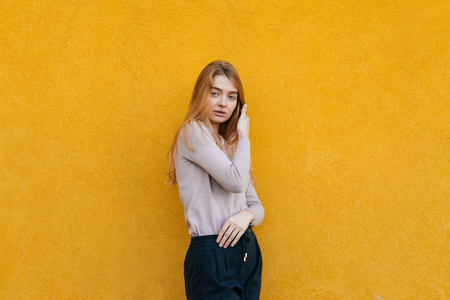 stylish beautiful young girl model with blond hair posing against a yellow wall