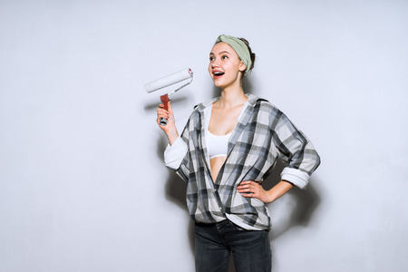 happy young girl painter holding a roller for painting walls Stock Photo