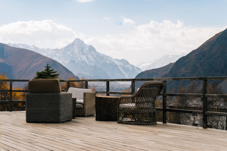 on the veranda are a table and chairs, a view of the majestic mountains under the blue sky Stock Photo