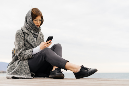 a stylish dark-haired girl in a gray coat and glasses sits by the sea, writes a message on the phone