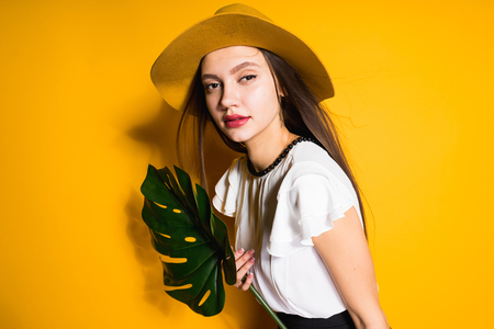 young attractive long-haired girl in a fashionable hat holds a green leaf, posing on a yellow background