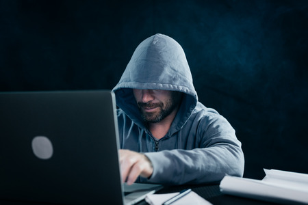 mysterious cunning man hides his face under the hood, hacks the laptop in the dark