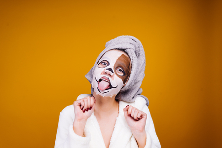 the woman after the shower has put or rendered a humidifying mask and shows tongue Stock Photo