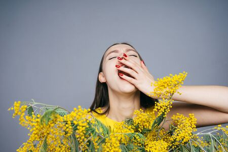woman among the little yellow flowers yawns, March 8, womens day