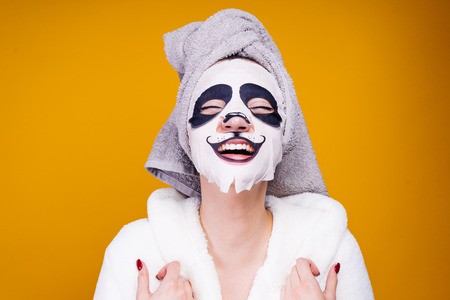 woman on a yellow background in a panda mask 스톡 콘텐츠