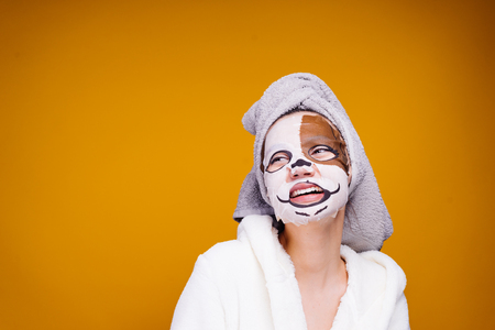 the happy woman has put or rendered a humidifying or wetting mask on the face and looks aside