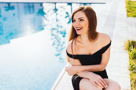 happy, rich, beautiful woman sits on the background of the pool on a sunny day Stock Photo