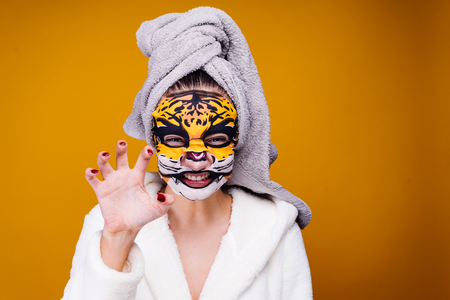 a woman stands on a yellow background in a tiger mask