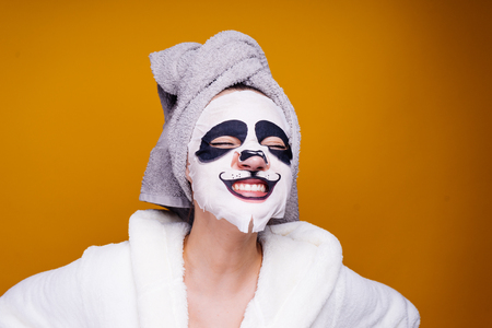 happy woman with a towel on her head apply moisturizing mask on face