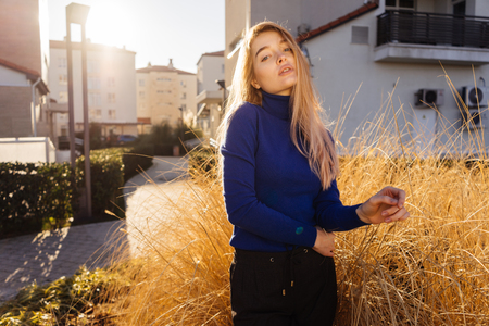 stylish beautiful young blond girl in blue sweater posing on city streets in the sun Stock Photo