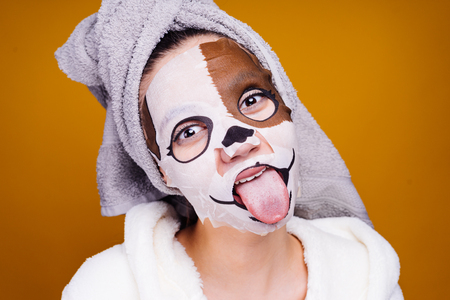 young girl with a towel on her head, on her face a mask with a picture of a muzzle of a dog, shows a tongue