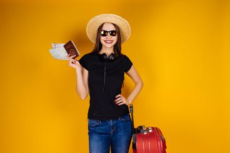 hermosa chica de pelo largo sosteniendo un automóvil de pasajeros y boletos para un avión, de vacaciones