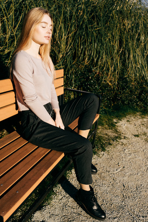 stylish young blond girl sitting on a bench in the sun, outdoors, eyes closed