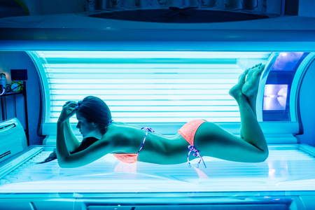 shapely beautiful young girl sunbathing in a solarium, wants a beautiful tanned skin 免版税图像