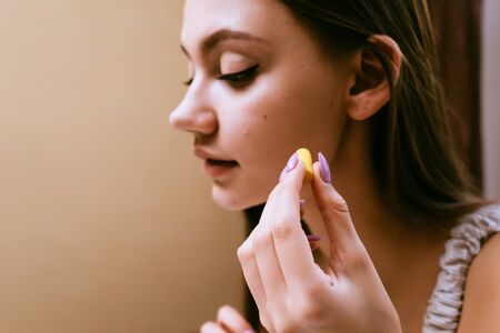 a young sleepy girl wants to sleep, inserts in her ears yellow earplugs against street noise Stock Photo