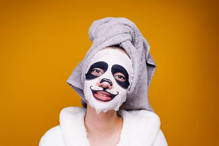 happy girl with a towel on her head smiling, on her face mask with a muzzle of a panda