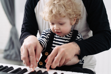 Dad plays with his young son, teaches to play the piano, family holidays Banque d'images