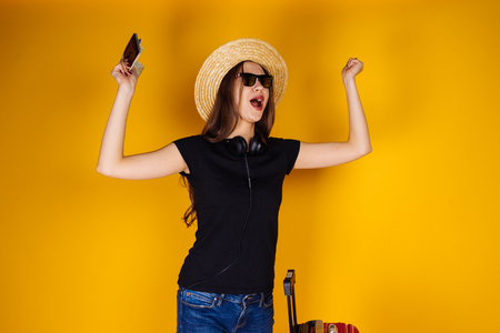happy young girl in sunglasses and a hat goes on a journey, rejoices, with a big red suitcase