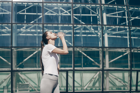 slender athletic girl drinks water, recovers from a complex long street workout