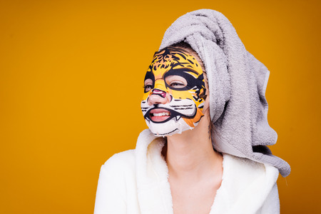 funny young girl with a towel on her head smiling, on her face a mask with a tigers face