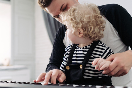 a friendly family, a young dad teaches to play his little curly son on the piano, spend time together