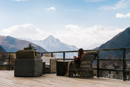 young girl traveler sits on a wooden veranda, enjoys the mountain scenery