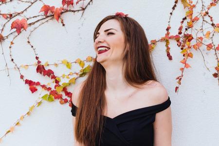 happy long-haired girl in black dress laughs, walks in her garden