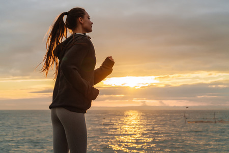 confident sports girl runs around the sea at sunset, trains before competitions