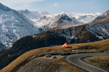 The magic nature, high mountains are covered with white snow, on the slope there is a tourist tent Stock Photo