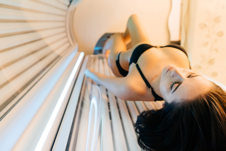 a slender girl in a black bathing suit sunbathing in a horizontal solarium, wants a beautiful tanned skin