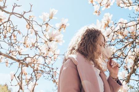 curly young woman in a pink coat sniffing a fragrant blooming magnolia, in the park Imagens