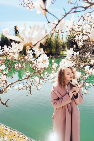 beautiful curly woman walking in a park by the lake, enjoying fragrant magnolia and sun Stock Photo