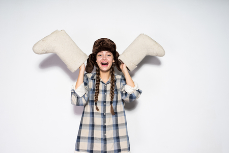 laughing young Russian girl with pigtails in a fur hat holds gray felt boots