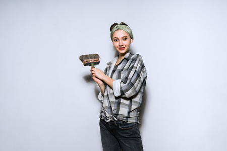 beautiful young girl in plaid shirt holding brush for painting walls, doing repairs in her apartment