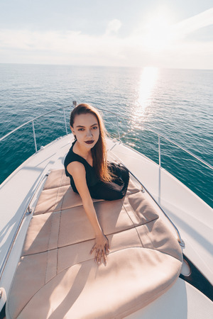 a luxurious elegant girl in black summer clothes sits on her white yacht, sails on the Caribbean sea
