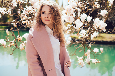 curly-haired woman wearing a pink coat posing next to a blooming fragrant magnolia in a park, ranks with a pond Stock Photo