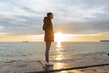 a tranquil, slender girl gets strength before jogging, stands by the sea in the rays of the evening sun and listens to music on headphones