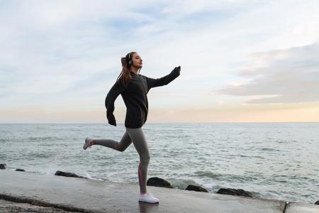 자신감이 빠른 어린 소녀가 바다 산책로를 돌아 다니며 헤드폰으로 음악을 듣는다. 스톡 콘텐츠 - 101589231