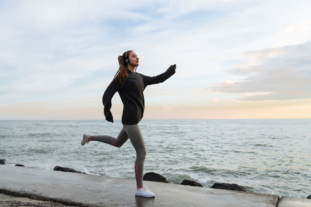 confident fast young girl runs around the sea promenade and listens to music on headphones Zdjęcie Seryjne